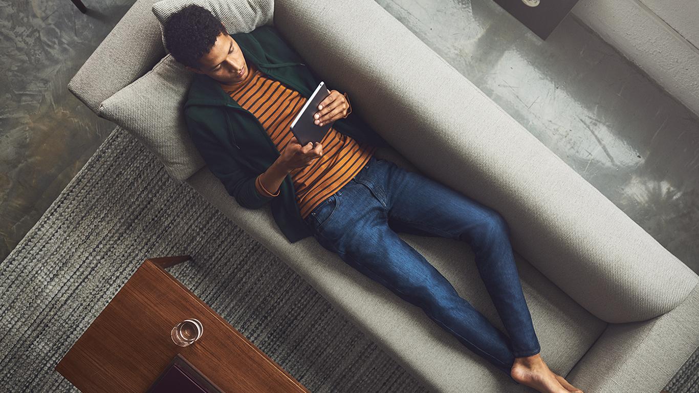 man reading on sofa wearing jeans